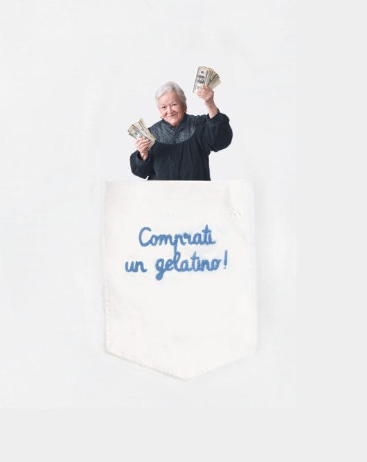 """Dettaglio della T-Shura maglietta con nonna nel taschino che dà soldi mancetta e dice """"Comprati un gelatino!"""" le magliette dei nipoti, la frase dei nonni è ricamata in azzurro t-sciura"""