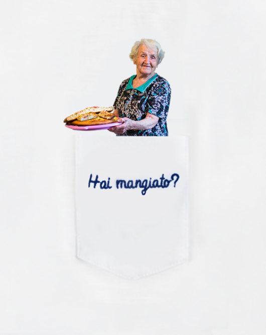 """Dettaglio della T-Shura maglietta con nonna che ha cucinato nel taschino che chiede """"Hai mangiato?"""" le magliette delle nonne, la frase dei nonni è ricamata in blu"""